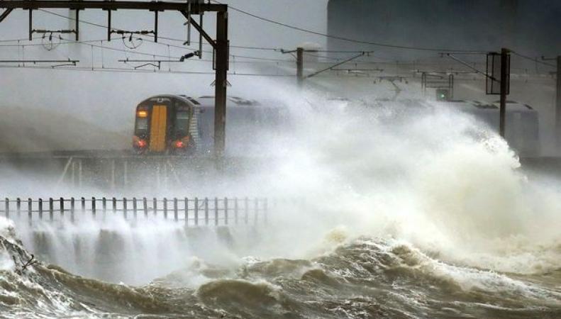 поезд на побережье в шторм