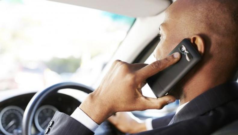 человек с телефоном за рулем