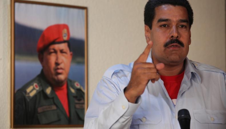 Николас Мадуро на фоне портрета Уго Чавеса